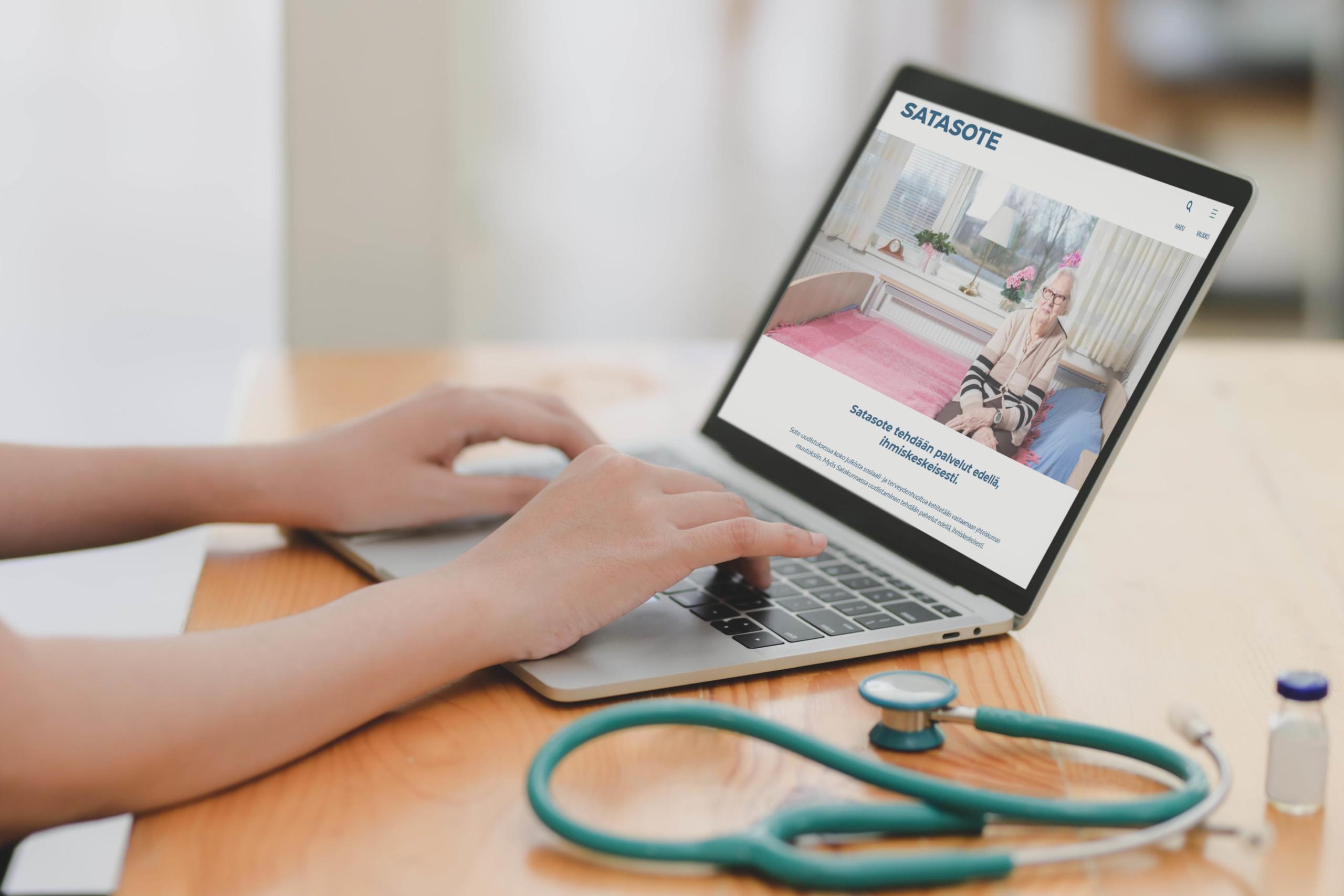 Terveydenhuollon työntekijä tietokoneen ääressä missä on avoinna Satasoten internetsivut