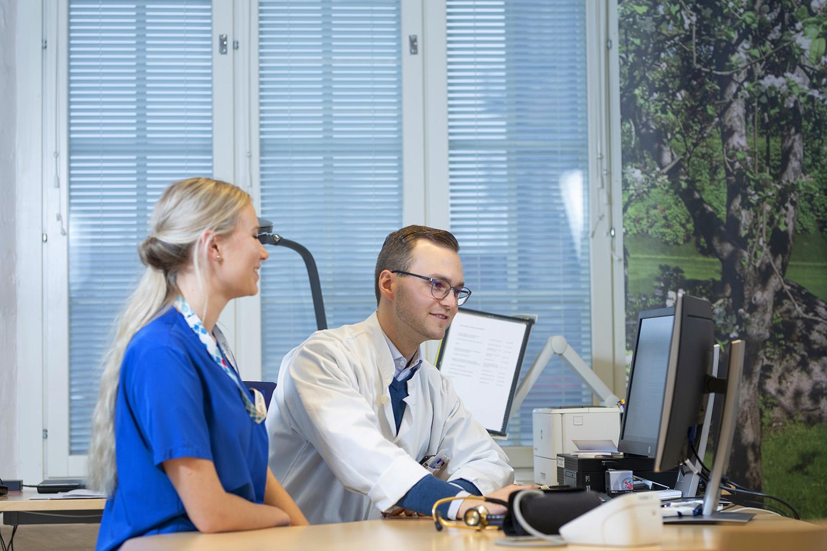 Hoitaja ja lääkäri keskustelevat tietokoneen äärellä