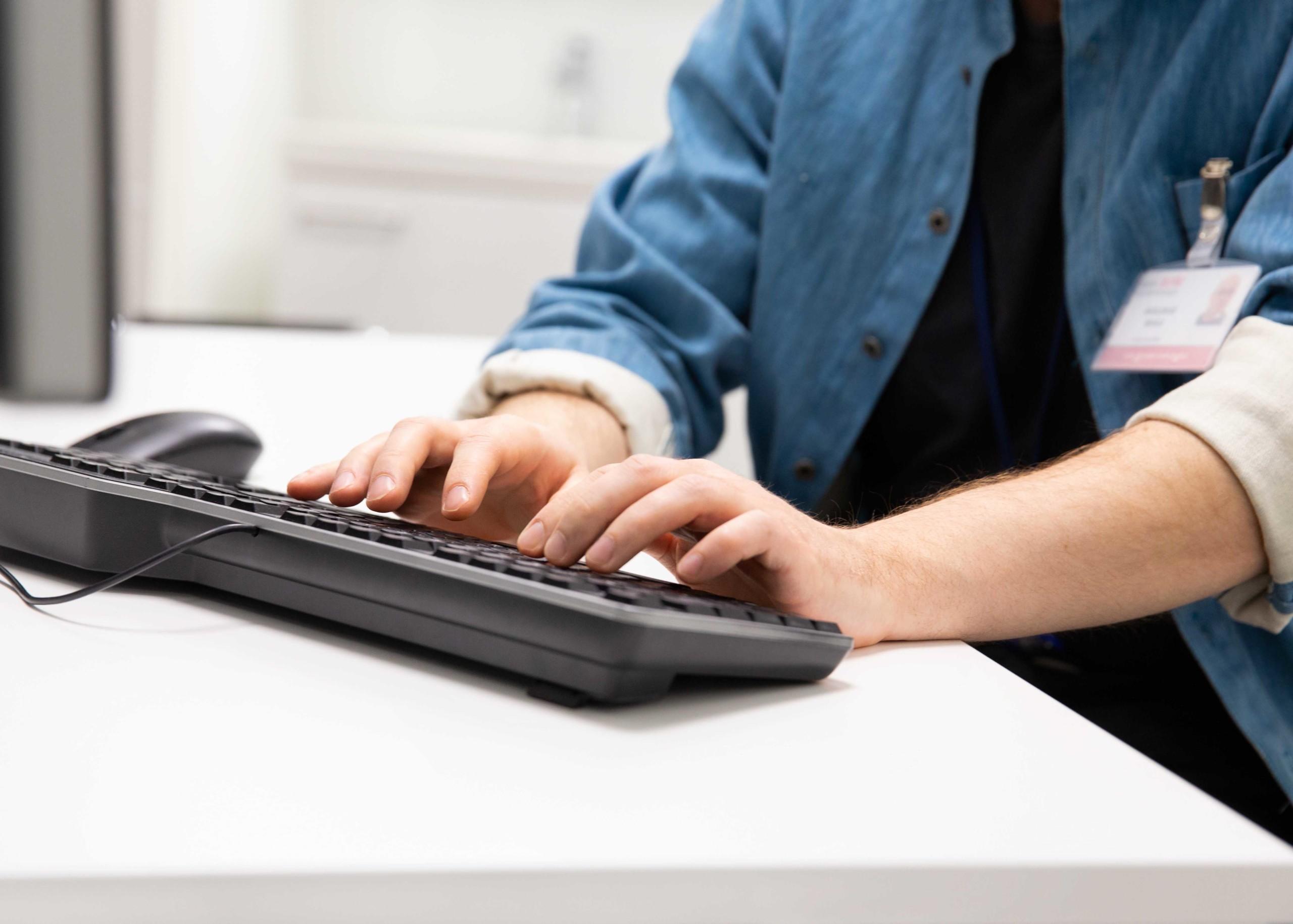 Siniseen paitaan pukeutunut henkilö kädet tietokoneen näppäimillä.