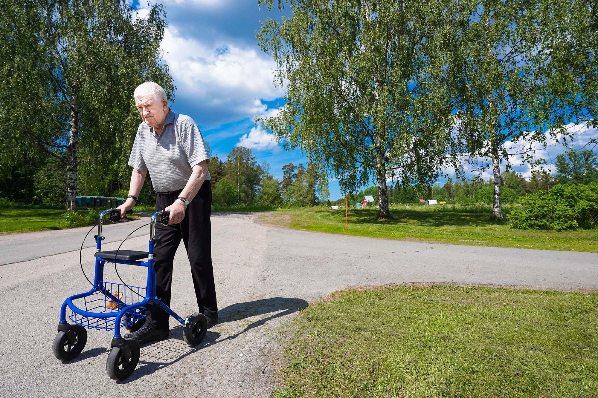 Eero Nieminen kävelee kesäisenä päivänä ulkona rollaattorin kanssa.