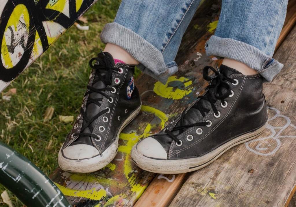 Farkkuihin ja tennareihin pukeutuneen henkilön jalat penkillä, missä on piirustuksia