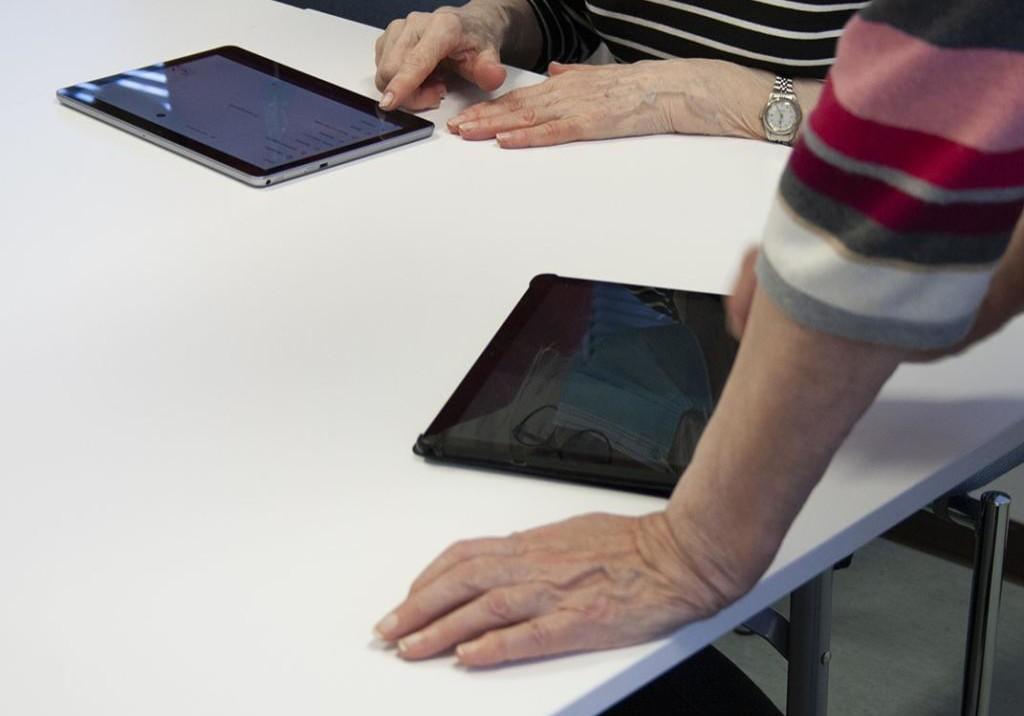 Kaksi henkilöä käyttävät tablet-tietokonetta pöydän ääressä