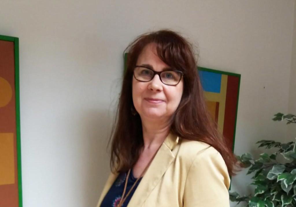Johanna Santanen seisomassa huoneessa, missä on viherkasvi ja tauluja seinillä