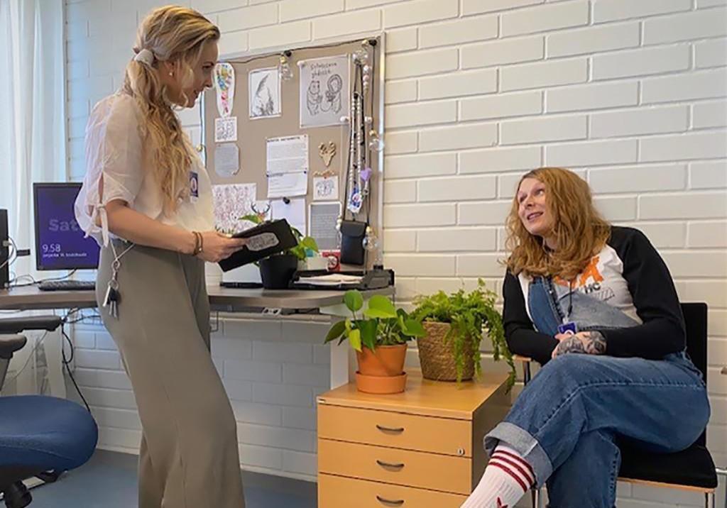 Johanna Stenroos ja Mari Hakulinen keskustelemassa työhuoneessa.