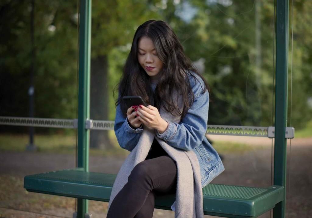 Tummahiuksinen nainen istuu bussipysäkillä ja käyttää puhelintaan