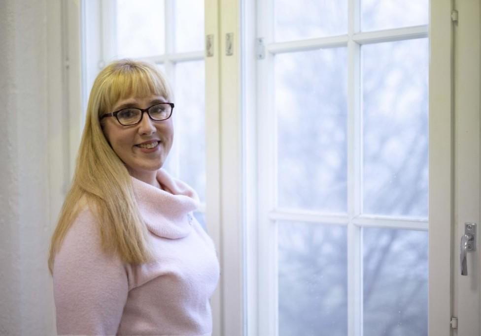 Sari Grönfors seisomassa ikkunan äärellä
