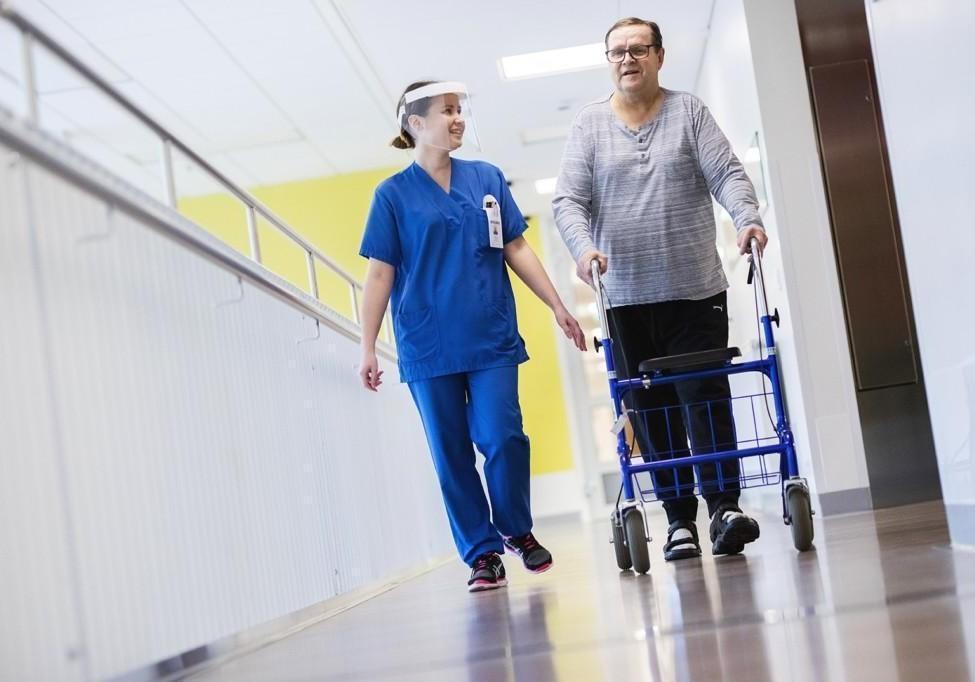 Iäkkäämpi mies kävelee rollaattorin avustuksella hoitajan kanssa.