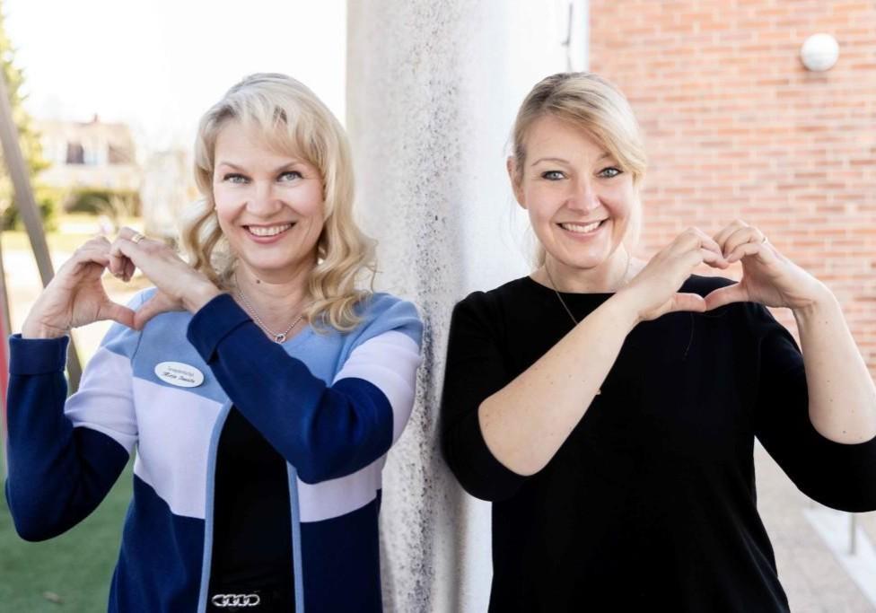 Mirja Isoviita ja Hanna Hilden seisovat ulkona tehden käsistä sydämen kuvan