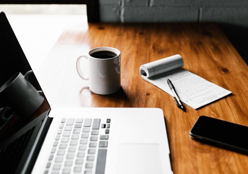 Tietokoneen äärellä kahvikuppi ja muistivihko