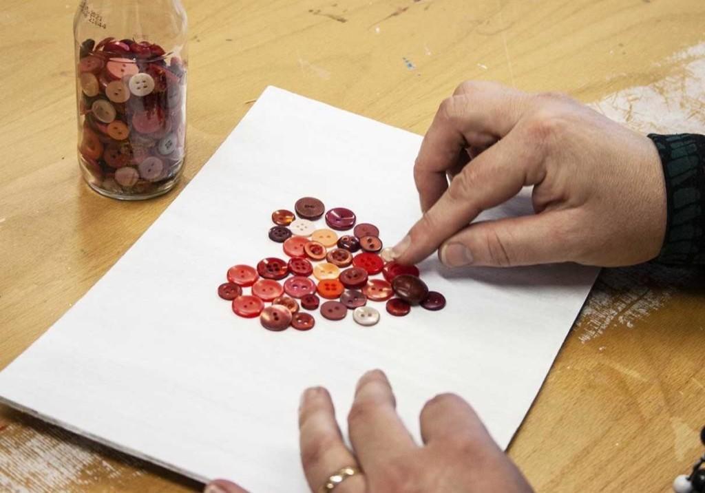 Henkilö asettelee nappeja sydämenmuotoon paperille