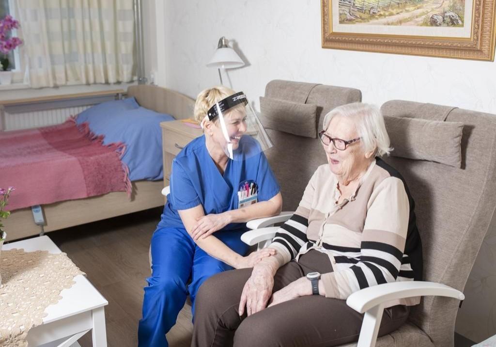 Hoitaja vanhuspalvelun asiakkaan kanssa sohvalla.